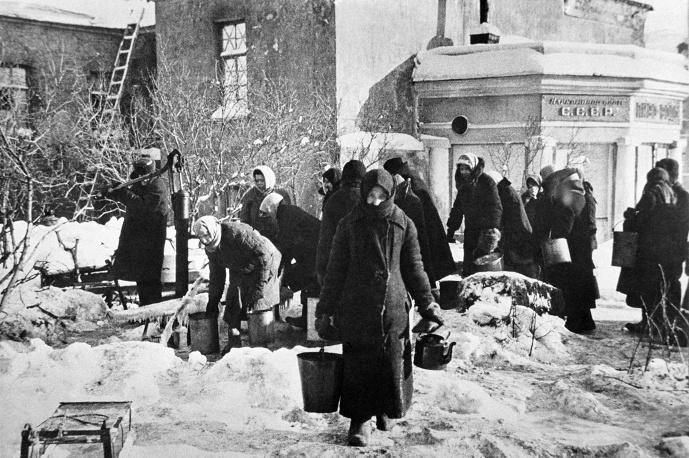 """Снабжение осажденного Ленинграда было налажено по Ладожскому озеру в конце ноября 1941 года. По """"Дороге жизни"""" подвозили боеприпасы, вооружение, продовольствие, эвакуировали больных и раненых. <br /><br />К окончанию блокады в Ленинграде осталось не более 800 тыс. жителей из 3 млн, проживавших в городе и пригороде до сентября 1941 года. От голода и обстрелов, по разным данным, погибли от 650 тыс. до 1 млн ленинградцев. Были ранены почти 34 тыс., без крова остались более 700 тыс. жителей. 1,7 млн человек в 1941-1942 гг. были эвакуированы по """"Дороге жизни"""" и по воздуху.<br /><br />В галерее ТАСС снимки военного времени, рассказывающие о жизни в осажденном городе<br /><br />Жители покидают дома, разрушенные немцами <br />© Фотохроника ТАСС/Борис Кудояров<br /><br />У водоразборной колонки, установленной на углу улицы Дзержинского и Загородного проспект <br />© Фотохроника ТАСС"""